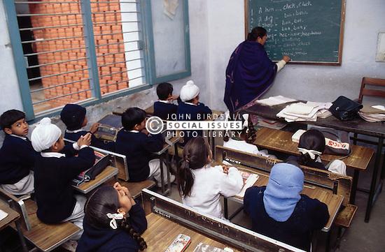 School girls and boys sitting at desks watching female teacher writing on whiteboard in senior secondary modern school; Punjabi University; Patiala; Punjab; India,
