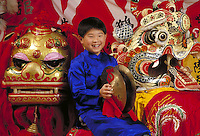 CHINESE-AMERICAN BOY WITH LION HEADS USED IN CHINESE NEW YEAR CELEBRATION. CHINESE AMERICAN BOY. SAN FRANCISCO CALIFORNIA.