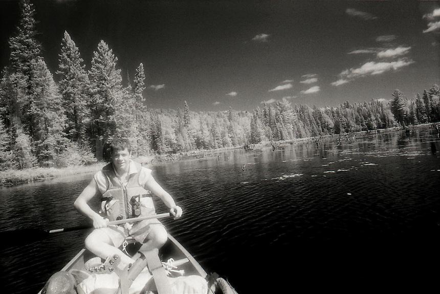 Teen boy canoeing in Algonquin Provincial Park, Ontario, Canada.