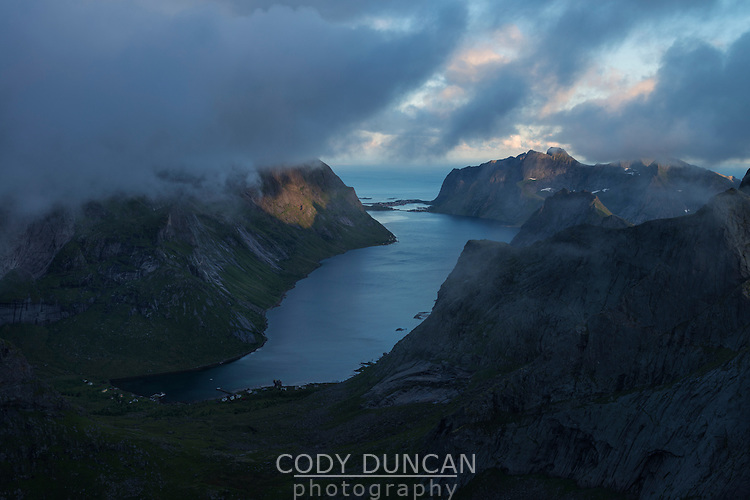 Clouds conceal mountain peaks over Kirkefjord from summit of Breiflogtind, Moskenesøy, Lofoten Islands, Norway