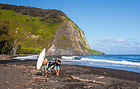 Boys with a surfboard and bodyboards walking on beach in Waipi'o Valley, Big Island.