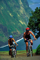 A couple biking up the steep road out of Waipio Valley on the Big Island