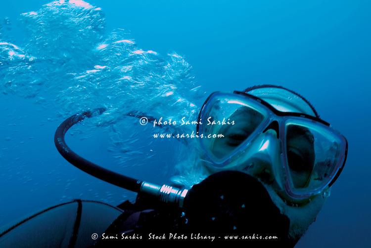 One scuba diver blowing bubbles underwater, Marseille, France.