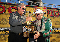 Nov 14, 2010; Pomona, CA, USA; NHRA funny car driver John Force (right) is presented with the championship trophy by NHRA president Tom Compton after clinching the 2010 funny car championship during the Auto Club Finals at Auto Club Raceway at Pomona. Mandatory Credit: Mark J. Rebilas-