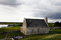 High angle view of Temple Connor, 1010, by Cathal O'Conor, and McCarthy's Tower, 12th century, in the distance, Clonmacnoise, County Offaly, Ireland, in the evening. Clonmacnoise was founded by St Ciaran, with the help of Diarmait Ui Cerbaill, Ireland's first Christian King. Picture by Manuel Cohen