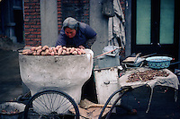 An old woman selling hot potatoes on the streets of Chengde checks to see whether they are cooked yet.