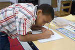 Oakland CA 2nd grader  concentrating on personal writing in class