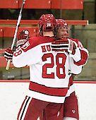 Chris Huxley (Harvard - 28) and Michael Biega (Harvard - 27) celebrate Biega's goal which made it 4-1 and stood as the game-winner. - The Harvard University Crimson defeated the St. Lawrence University Saints 4-3 on senior night Saturday, February 26, 2011, at Bright Hockey Center in Cambridge, Massachusetts.