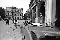 Boys practice flying kicks at the hulk of an old auto on the Plaza del Cristo in Havana.