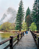 USA, California, Yosemite National Park, kids run across a bridge over the Merced River near Curry Village