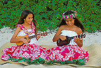 Two girls in orchid leis, one with haku head lei, playing ukulele on the beach