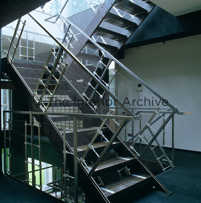 A dramatic stainless steel staircase adds a sculptural if industrial quality to the interior of this house