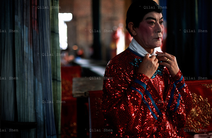 "Opera042 20030612 SHANXI, CHINA: 71 year old veteran Jin Opera performer Wang Heqi buttons a collar in preparation to perform a rare male role for a small skit backstage at a village in Shanxi Province, China 12 June 2003. Known around the province as ""Girl 13"" because he specialized in female roles all his life after he became a star on stage at the early age of 13, Mr. Wang finally retired in late 2003 after performing for 57 years."