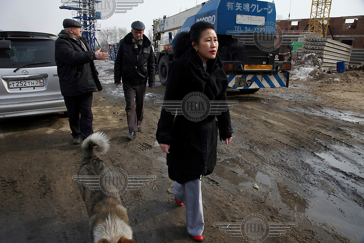 Chinese entrepreneur Li Lihua with two Russian engineers who work for her developing real estate in the Russian city of Blagoveshchensk, just across the border from China.