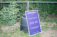 A campaign sign rests against a backyard composter as Democratic presidential candidate and spiritual guru Marianne Williamson speaks to a small crowd in the back yard of Kathleen O'Donnell at a campaign house party event in Keene, New Hampshire, on Wed., May 22, 2019.