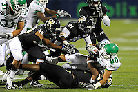 1 September 2011:  FIU defensive back Chuck Grace (21), defensive back Sam Miller (39), and linebacker Markeith Russell (22) combine to tackle North Texas wide receiver Brelan Chancellor (80) in the second half as the FIU Golden Panthers defeated the University of North Texas, 41-16, at University Park Stadium in Miami, Florida.