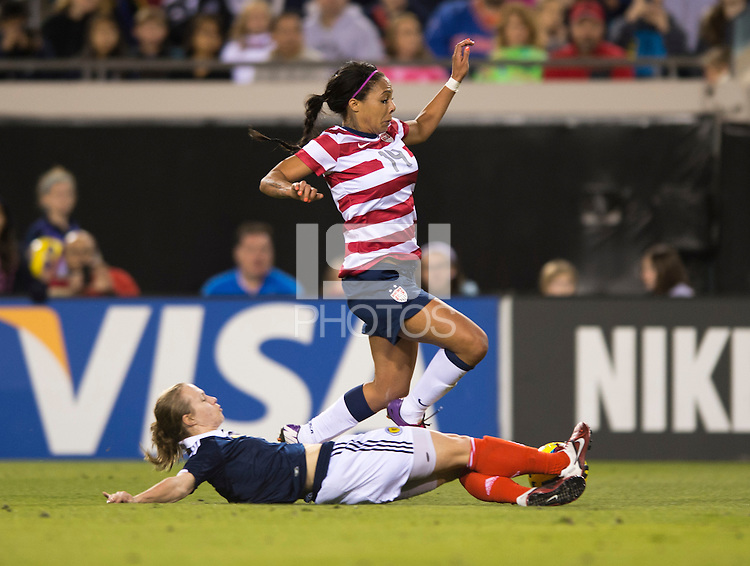 Sydney Leroux (14) of the USWNT has the ball tackled away from her by Eilish McSorley (4) of Scotland during the game at EverBank Field in Jacksonville, Florida.  The USWNT defeated Scotland, 4-1.