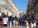People shopping in a pedestrianised street of shops in the city centre of Malaga, Spain