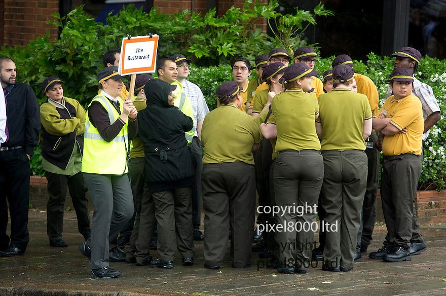 Pics shows: More than  100 McDonald's workers got drenched due to a badly timed fire drill at the East Finchley headquarters the &quot;Hamburger University&quot; today.<br /> <br /> Many were left cursing Ronald McDonald as they  used coats and rally point signs to cover their heads from the chilly wind and rain as they stood in the street.<br /> <br /> Some managed grab an umbrella but others just stood in there shirts and t-shirts in the cold for 15 miserable minutes before they waited for the all clear.<br /> <br /> <br /> <br /> <br /> <br /> picture by Gavin Rodgers/ Pixel