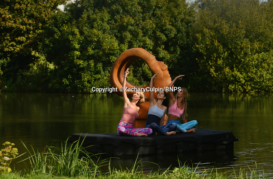 BNPS.co.uk (01202 558833)<br /> Pic: ZacharyCulpin/BNPS<br /> <br /> ...and relax <br /> <br /> A yoga class by a takes place on the water in front of the sculpture 'Search for Enlightenment' by sculptor and owner of Sculpture by the Lakes, Simon Gudgeon. <br /> Pictured: (from left) Gail Taylor, Martha Manson and Pip Taverner.<br /> <br /> Sculpture by the Lakes near Dorchester in Dorset will be hosting a brand new 3 day festival, 'Wellbeing by the Lakes'. The event 'aims to explore explore what it means to be mindful and how to live well in our fast-paced modern world' it will run from Thursday 19th September – Saturday 21st September 2019