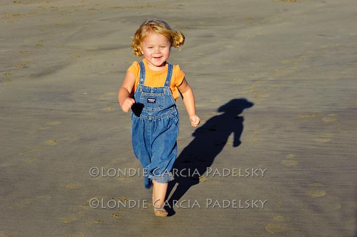 Little girl having fun on the beach, Central Coast of California
