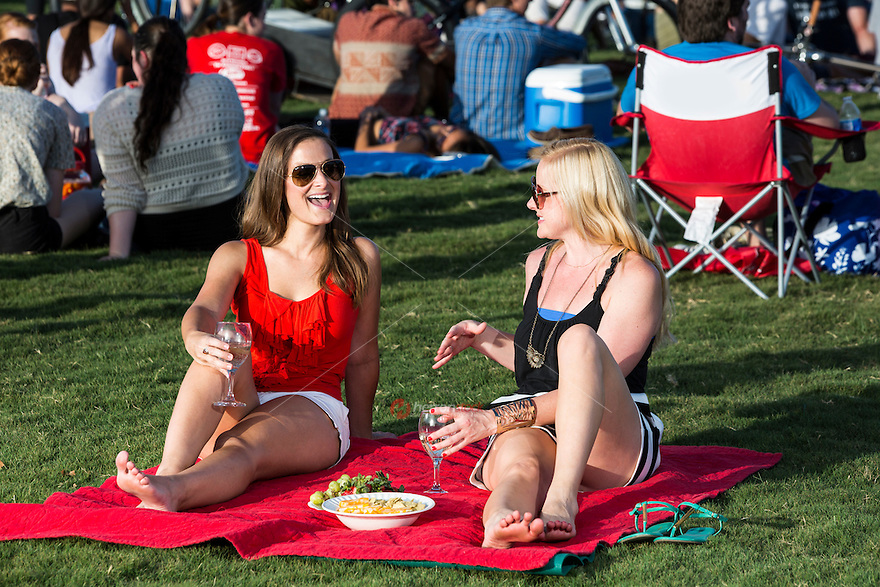 Two nice looking Austin women drinking wine during a picnic at the the Blues On The Green free summertime concert series in Zilker Park. Blues on the Green is a free, live music summer concert series. Take your blankets, lawn chairs, ice chest, pets and join in the fun. The music starts at 8 p.m.