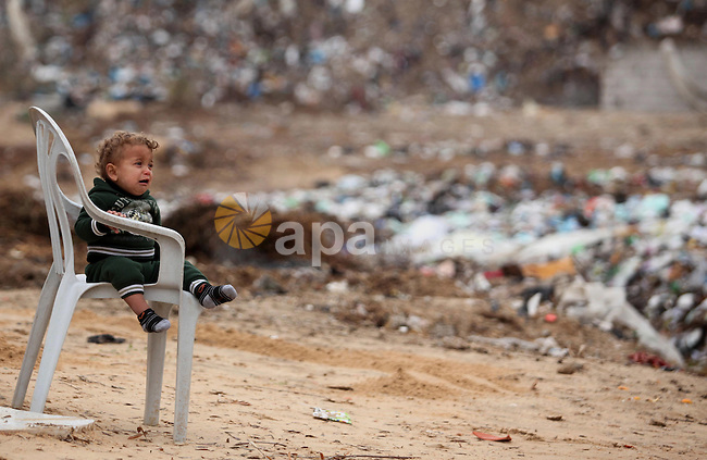 A Palestinian child stand outside his dwelling covered with plastic sheet in Khan Younis in the southern Gaza Strip December 19, 2016. Photo by Ashraf Amra