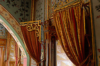 Curtains over a doorway hang from gilded brackets