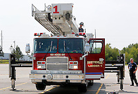 NWA Democrat-Gazette/DAVID GOTTSCHALK  Ryan Powers, with the city of Fayetteville Fire Department, brings the ladder platform back down into position Monday, August 31, 2015 during a weekly truck check in Fayetteville. The Ladder One truck is run through an operation and maintenance check that includes all ladder functions, engine maintenance and check of other operations.