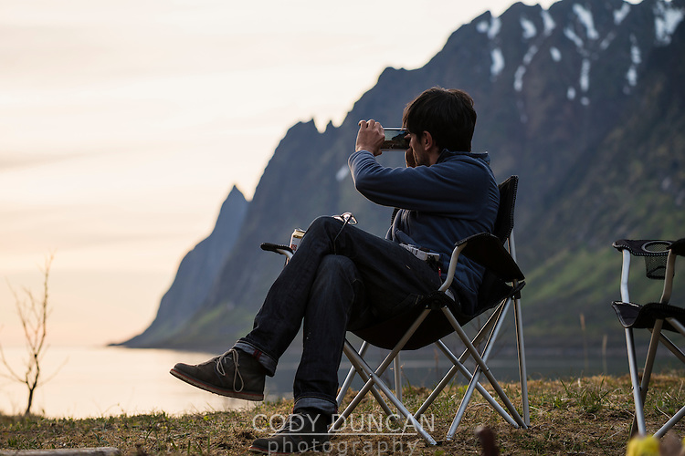 Person takes photo of sunset from camp with iphone, Ersfjord, Senja, Norway
