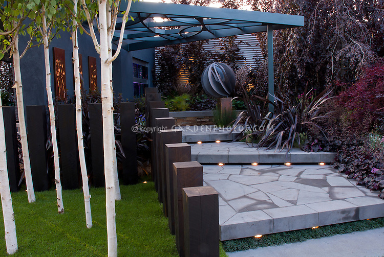 Beautiful blue tones patio steps with built-in night lighting, birch trees, landscaping, arbor, garden ornament in evening