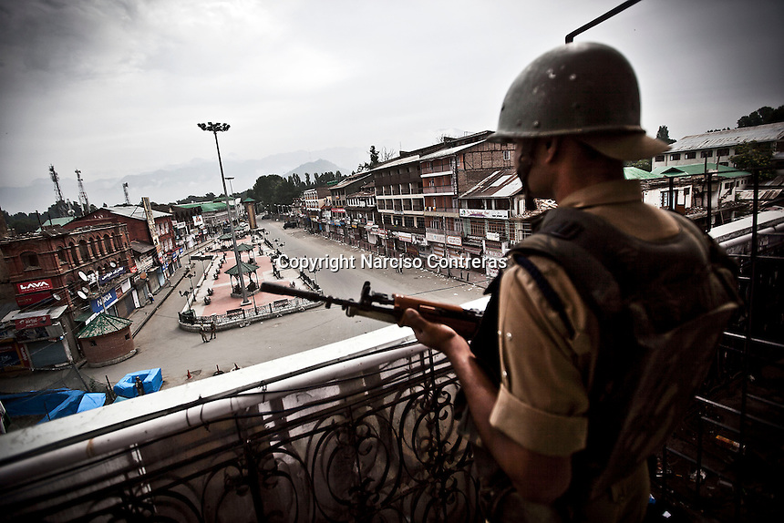 Indian paramilitary soldier stands guard from a balcony building at Lal Chow area in Srinagar as India is celebrating the Independence day. The curfew was declared into the most conflictive areas across the city and districts into the Kashmir valley. Security has been beefed up by indian paramilitary forces (CRPF), army and police on streets and check points.