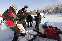 February 16, 2013  Logistics volunteers (L to R) Al Kiefer, Jason Spindler and Chris Blankenship help load volunteer Iditarod Air Force pilot Mike Swalling's plane at the Willow airport as musher food, straw, HEET and people food is flown to the 4 checkpoints on the east side the Alaska Range. ..Iditarod 2013 Photo Copyright Jeff Schultz  -- Do not reproduce without written permission
