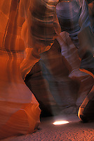 Antelope slot canyon cavern with a light beam to enhance the shapes and curves of natural sandstone created by erosion near Lake Powell and Page Arizona