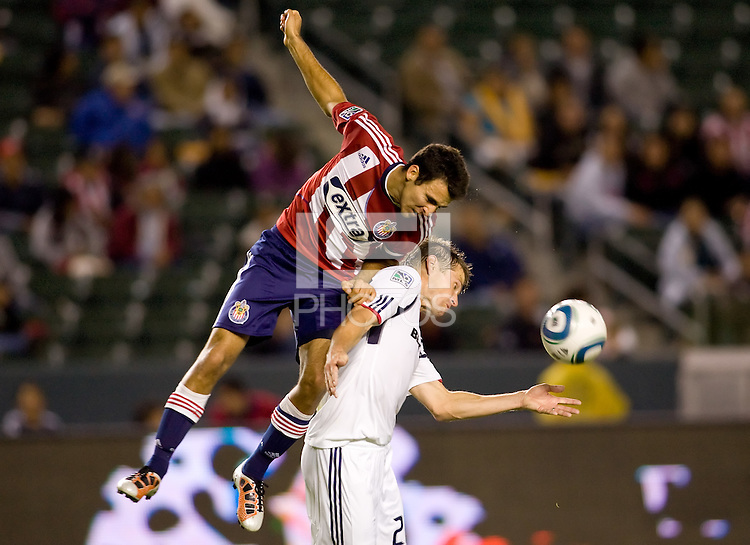 Chivas USA midfielder Jonathan Bornstein (r) goes over the top of Chicago Fire veteran Brian McBride (w) in both of there last matches in the MLS together. The Chicago Fire defeated CD Chivas USA 3-1 at Home Depot Center stadium in Carson, California on Saturday October 23, 2010.