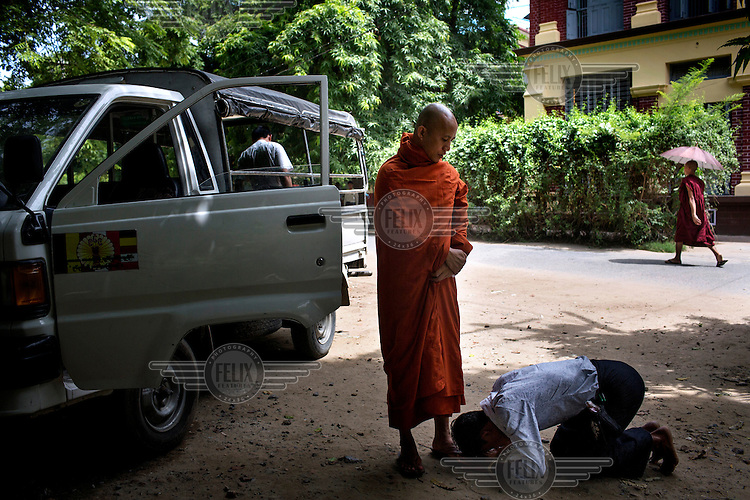 A supporter of U Wirathu, the spiritual leader of the Buddhist nationalist 969 Movement bows at his feet outside his quarters at the New Maesoeyin Monastery in Mandalay. U Wirathu is an abbot in the New Maesoeyin Monastery where he leads about 60 monks and has influence over more than 2,500 residing there. He travels the country giving sermons to religious and laypeople encouraging Buddhists to shun Muslim business and communities. /Felix Features
