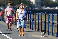 Pictured: A lady walks her dog during the sunny weather at Mumbles, near Swansea, Wales, UK. Thursday 19 September 2019