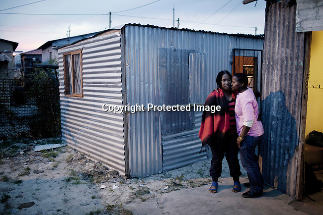CAPE TOWN, SOUTH AFRICA - OCTOBER 19: Siya Mcuta (l) with her girlfriend Zikona Moloyinyan hugs outside a gay only bar on October 19, 2011 in Khayelitsha outside Cape Town, South Africa. Cape Town is a city known for tolerating gays and lesbians except in the townships where they get harassed and often attacked. Some women have been raped in so called corrective rape, where men rapes them to make them women again. They can't show their love freely on the streets in the townships so they usually have to meet in houses and this bar. (Photo by Per-Anders Pettersson)