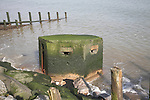 Old pill box fallen into the sea. Coastal erosion and damaged sea defences at East Lane, Bawdsey, Suffolk, England