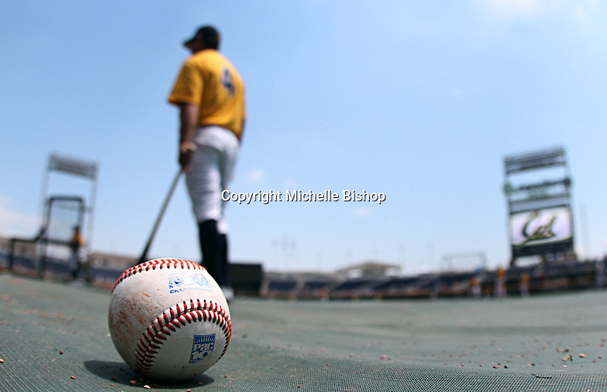 A baseball rests on the field at TD Ameritrade Park as Cal Assistant Coach Brad Sanfilippo helps warm-up his players before a 2011 College World Series game in Omaha, Neb. (Photo by Michelle Bishop)..