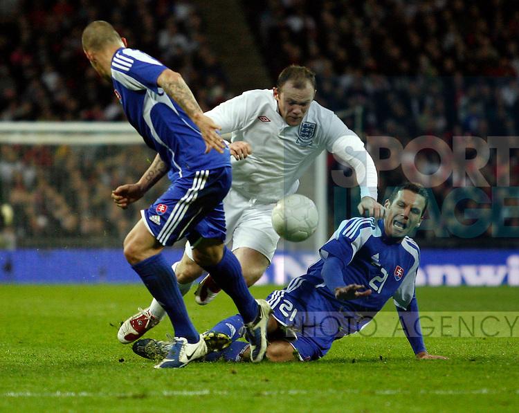 England's Wayne Ronney gets fouled by Slovakia's Josef Valachovic