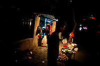 People stand near a street corner fruit market at night in Nanjing, China.