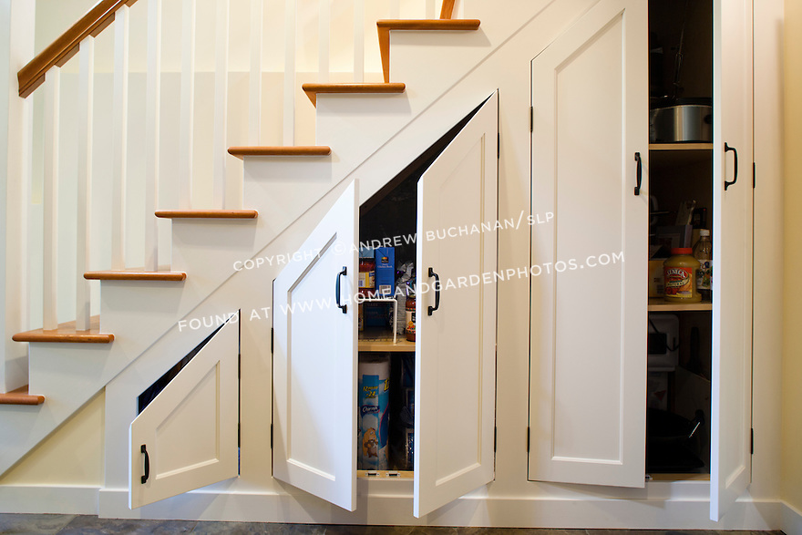 custom cabinets built under the stairs maximize storage in this newly remodeled basement this image
