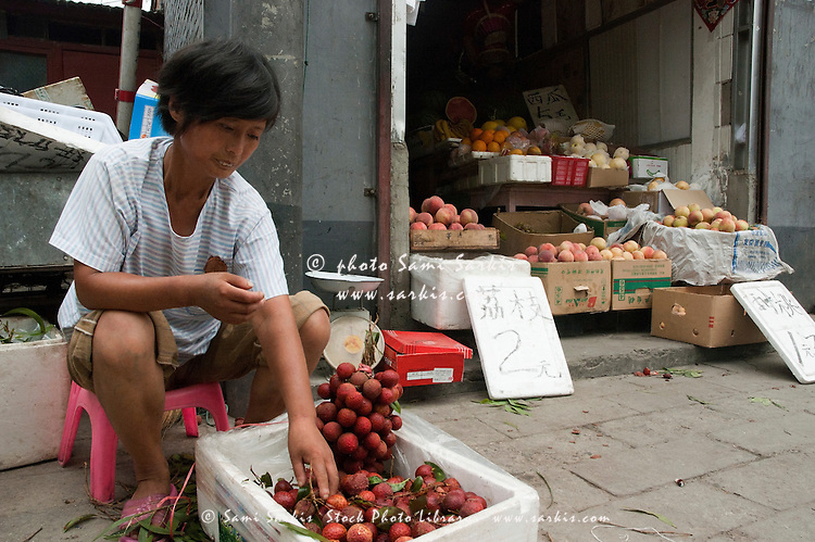 Woman selling lychees from a fruit stall, Hutong district, Beijing, China.