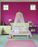 In a girl's bedroom a shocking pink wall sets off a striped rug and bedding in softer tones
