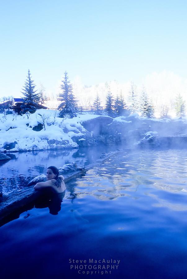 Young woman enjoying a winter soak in the snow-lined pools at Strawberry Park Hot Springs, Steamboat Springs, Colorado