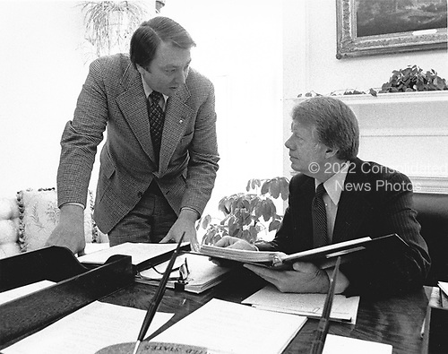 United States President Jimmy Carter, right, meets with his Assistant for Congressional Liaison, Frank Moore, left, in the Oval Office of the White House in Washington, DC on February 9, 1977.<br /> Credit: White House via CNP