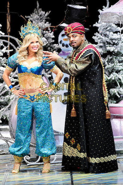 MELINDA MESSENGER & DON GILET.First Family Entertainment theatre company's annual group Pantomime photocall at Piccadilly Theatre, London, England..November 26th, 2010.stage costume panto pantomime full length blue gold trousers top belly stomach midriff genie crown black turban on hip hands side .CAP/CAS.©Bob Cass/Capital Pictures.