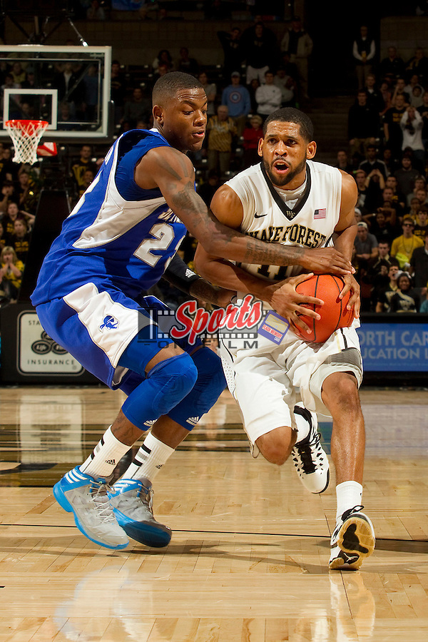 C.J. Harris (11) of the Wake Forest Demon Deacons draws contact from Fuquan Edwin (23) of the Seton Hall Pirates as he tries to drive past him during second half action at the LJVM Coliseum on December 8, 2012 in Winston-Salem, North Carolina.  The Pirates defeated the Demon Deacons 71-67.    (Brian Westerholt/Sports On Film)