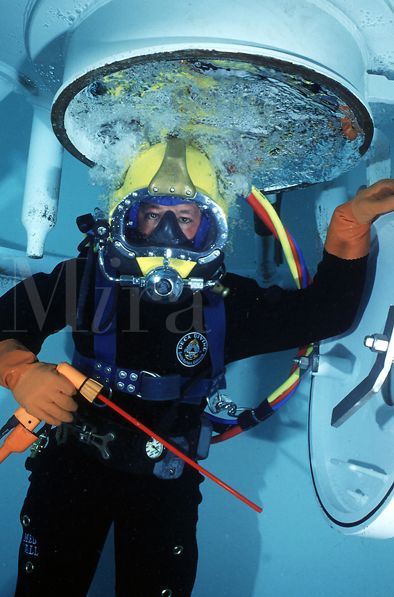 Commercial diver with underwater cutting torch outside diving bell (deep-sea diver)